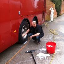 Richard pretending to clean the bus wheels on a One Direction tour.